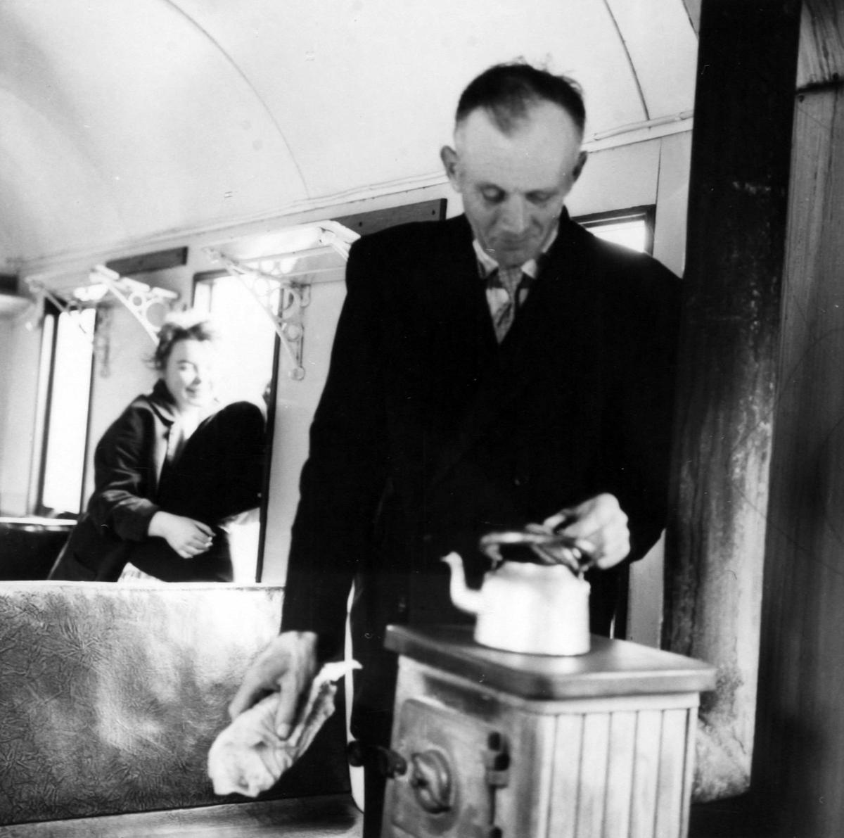 Vogn BCo3 - interiør. Reisende (later som om han) koker kaffe på vedovnen.
