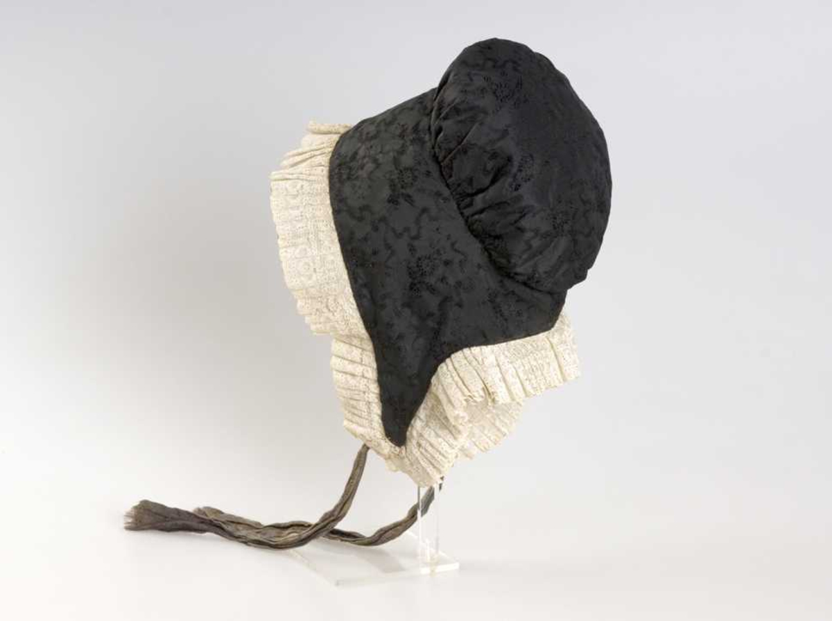 Rynkelue av typen høglue. Svart silke i hovedstoff, med lerretsfôr, og blonde av hvitt bomull. Hovedstoff har innvevde blomstermotiv og rankeformer, svart på svart. Hakebånd i silke.