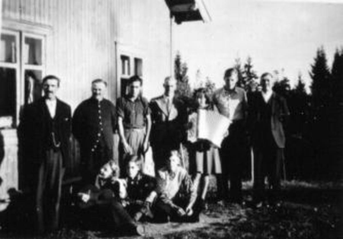 Helgemoro i Fløttum under Mellom-Kise, Nes, Hedmark. Bak fra venstre er Petter Lundstein (1888-1969), Johannes Fløttum (1893-1965), Johan Fløttum f.1920, Tore Solvang, ukjent,, Jørgen Fløttum f.1921, Kristian Rosenlund (1884-1960). Foran fra venstre er ukjent, Magne Fløttum f.1926, Kåre Rosenlund f.1926. Gitar og trekkspill.