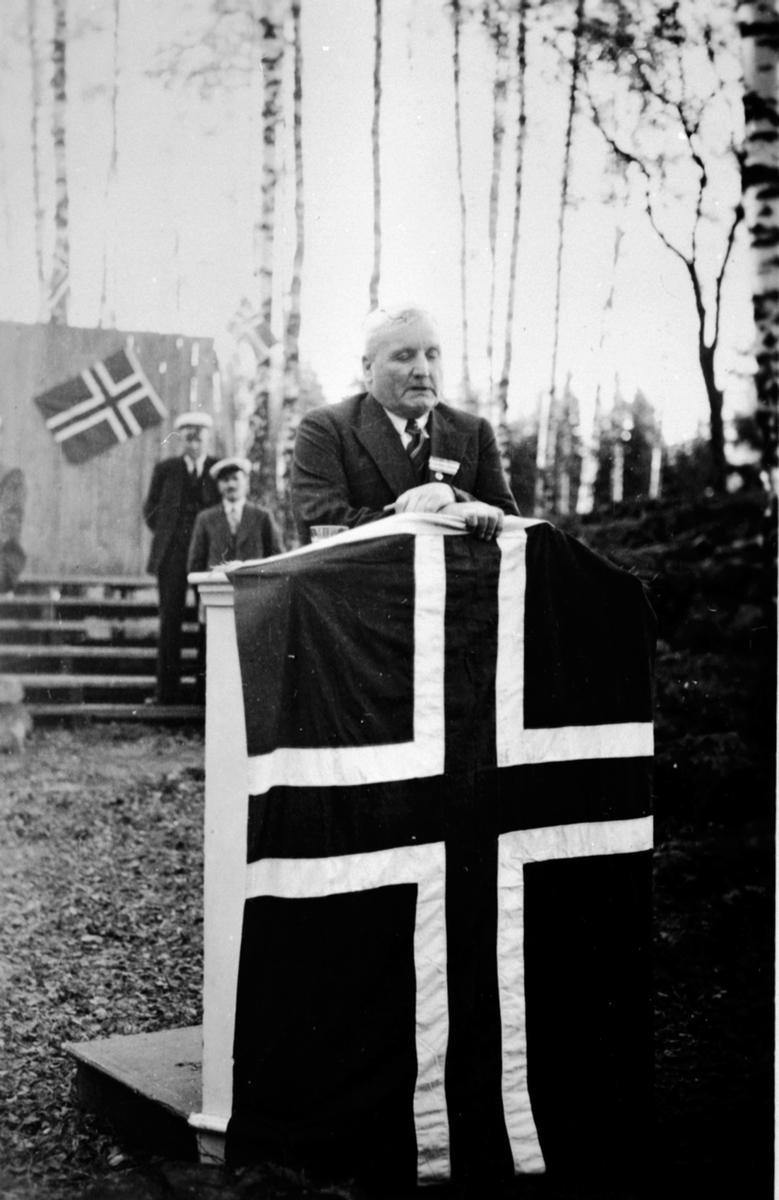 Disponent ved Moelven Brug, Severin Myrbakken på talerstol med flagg, 17 maitaler, Moelv.