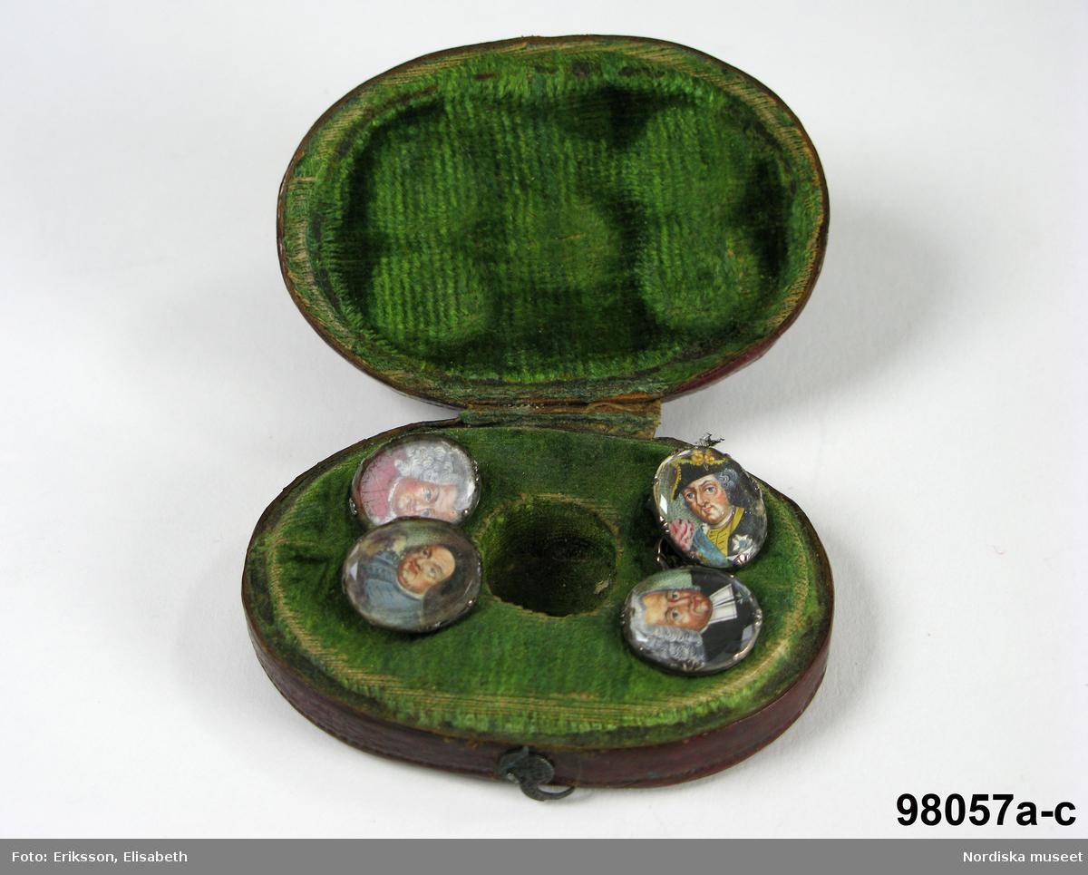 """Manschettknappar, två par, miniatyrer. 1700-tals mitt.  Silver, glas. Saknar stämplar. På varje knapp ett ovalt porträtt i miniatyr i silverinfattning, baksidan räfflad, knapparna förenade två och två, på den ena föreningslänken. """"I H"""" i genombrutit arbete, den andra föreningslänken senare ersättning. Manschettknapparna hölls i ett rött marokäng (getskinn) etui. (katalogiseringen gäller a-c)"""