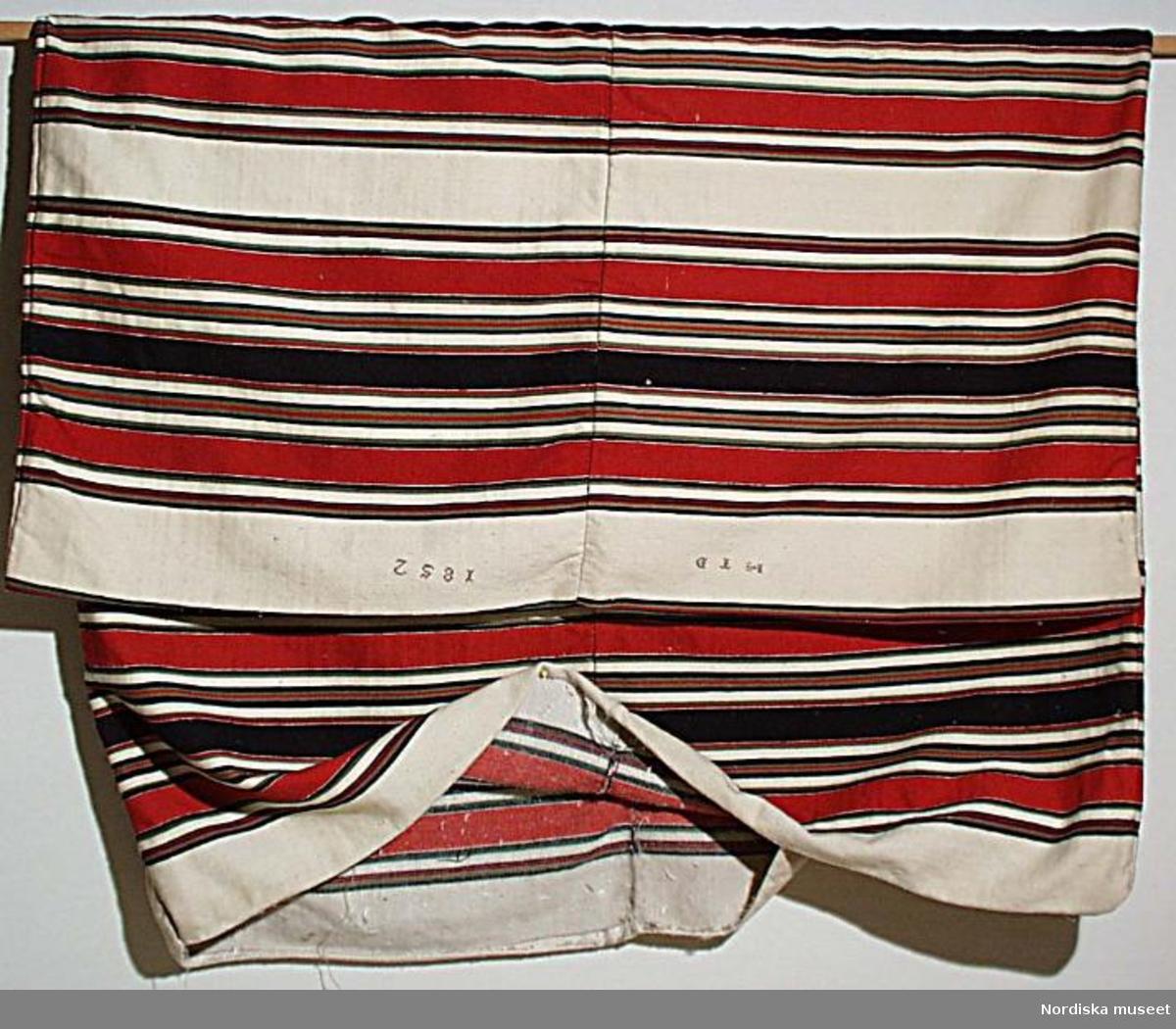 Bolstervar med  varp av lingarn, inslag av 1-tr. ullgarn i vitt med ränder i rött, grönt, svart och blått, vävt i satin ( ej kontrollerat, bör göras efter utställning), vävt i 2 våder, hopsytt för hand på mitten. Märkt med korsstygn i lila ullgarn H T D 1852 i ena änden. Har varit fyllt med dun.  Berit Eldvik april 2005