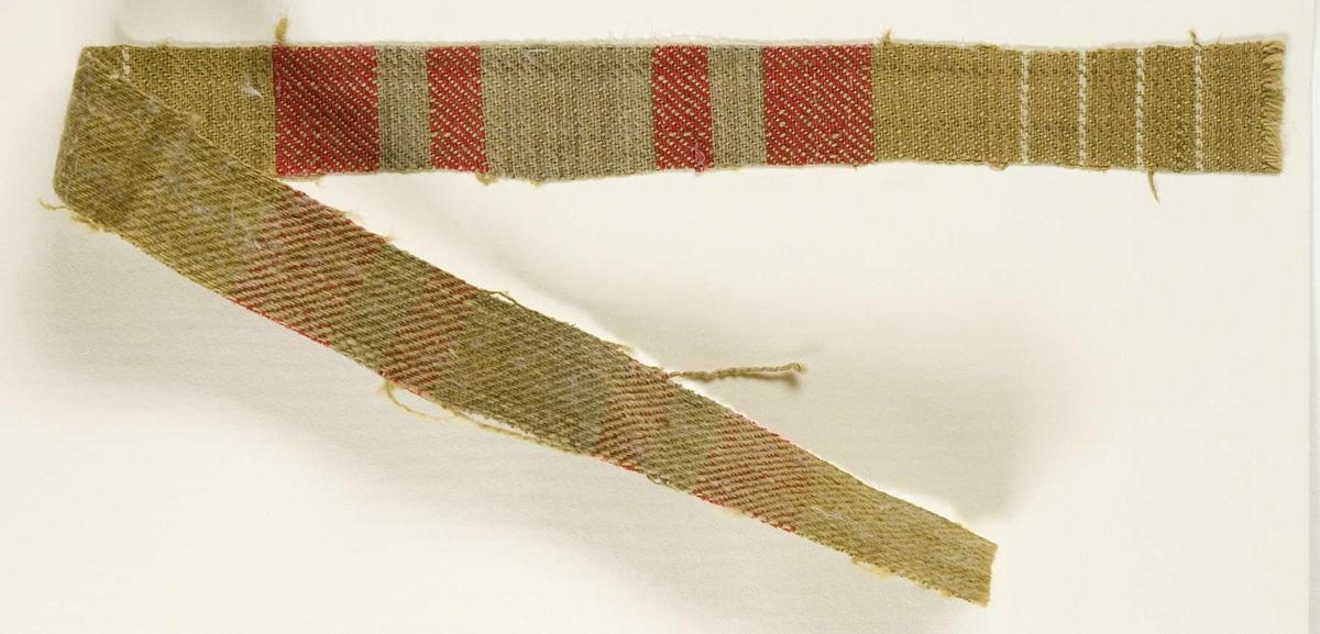 """Vävprov ämnat för bolstervarstyg vävt med bomullsgarn, kypert. Randigt i rött, vitt och grönt. Vävprovet är uppklistrat på en kartong i storleken 22 x 28 cm. I övre högra hörnet finns en stämpel """"Uppsala läns hemslöjdsförening"""" och ett handskrivet nummer, """"A.1611""""."""