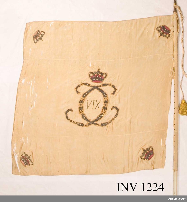 """På det gulvita kyprade fansidenet sitter i mitten ett broderat monogram föreställande två motställda """"C"""" inneslutande """"XIV"""". Broderiet utfört i plattsöm med silke och silvertråd. Ovanför monogrammet sitter en kunglig krona utförd i plattsöm med foder i rött silke. I fanans hörn sitter snedställda kronor i rött silke. Fanspetsen har Karl XIV Johans monogram, dock mycket ärgat. Fanstången är gulvitmålad. Kravatten, den lilla del som återstår, är uppsydd på ett bomullsband.   Samhörande nr är 25394:1, 25394:2, 1224-1228."""