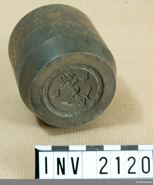 Blir i färdigt skick en förgylld mässingsplatta med krönt ankare med ankartåg och tre kronor i relief på matt botten. Det hela omgivet av lagerornament. På baksidan en fästanordning. Utföres även i vit metall. Källa: Uni Fl 854-862.  Samhörande nr är 1677-1699, 1800-1899, 2100-2123.