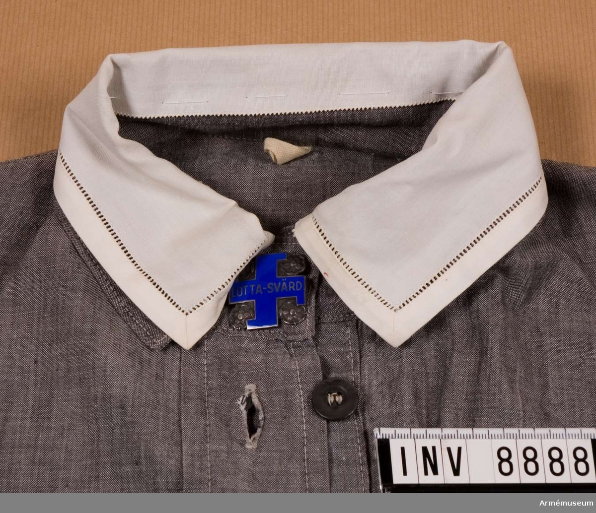 Vit löskrage till lottaklänning Finland. Sydd med hålsöm i ytterkanten på tre sidor i vitt tyg. Kragen är fasttråcklad över klänningens krage.