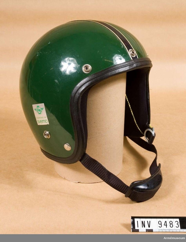 """Storlek 56-57. Motorcykelhjälm av glasfiber, vadderad med skumplast och överklädd med trikåtyg av nylon. Hakskydd av plast. Rem av  nylon. Runt kanten löper en plastlist. Fem knäppen finns för visir, som dock saknas.  Hjälmen är utvändigt mörkgrön och har på ena sidan en påklistrad dekal i vitt, rött och blått med texten: """"Tommy Helmet"""", och på andra sidan en i silver och grönt med texten: """"SM Godkänd av Svemo"""".   Rem, hakskydd och lister är svarta. Likaså hjälmens insida, som har en lapp med texten: """"Orginal, 56-57, Tommy, Godkjent modell fra Teknisk isolering, Drammen-Norway""""."""