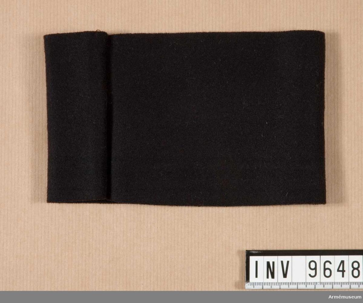 Samhörande nr i gåvan är 9605-9650 + 9659-9666.Sorgband. Ylle.Ett svart klädesband att bäras över vänster överärm vid sorg.Ang sorg se UniA sid 15 nr 16, 1-5.