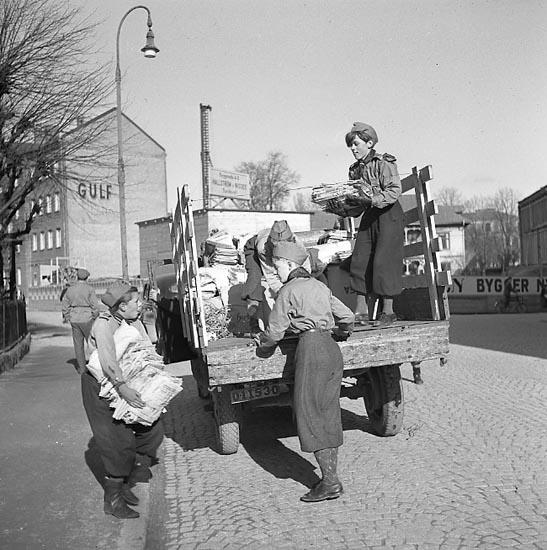 Ungdomar samlar in papper från hem i Uddevalla i april 1947. En lastbil transporterar tidningsbuntarna.