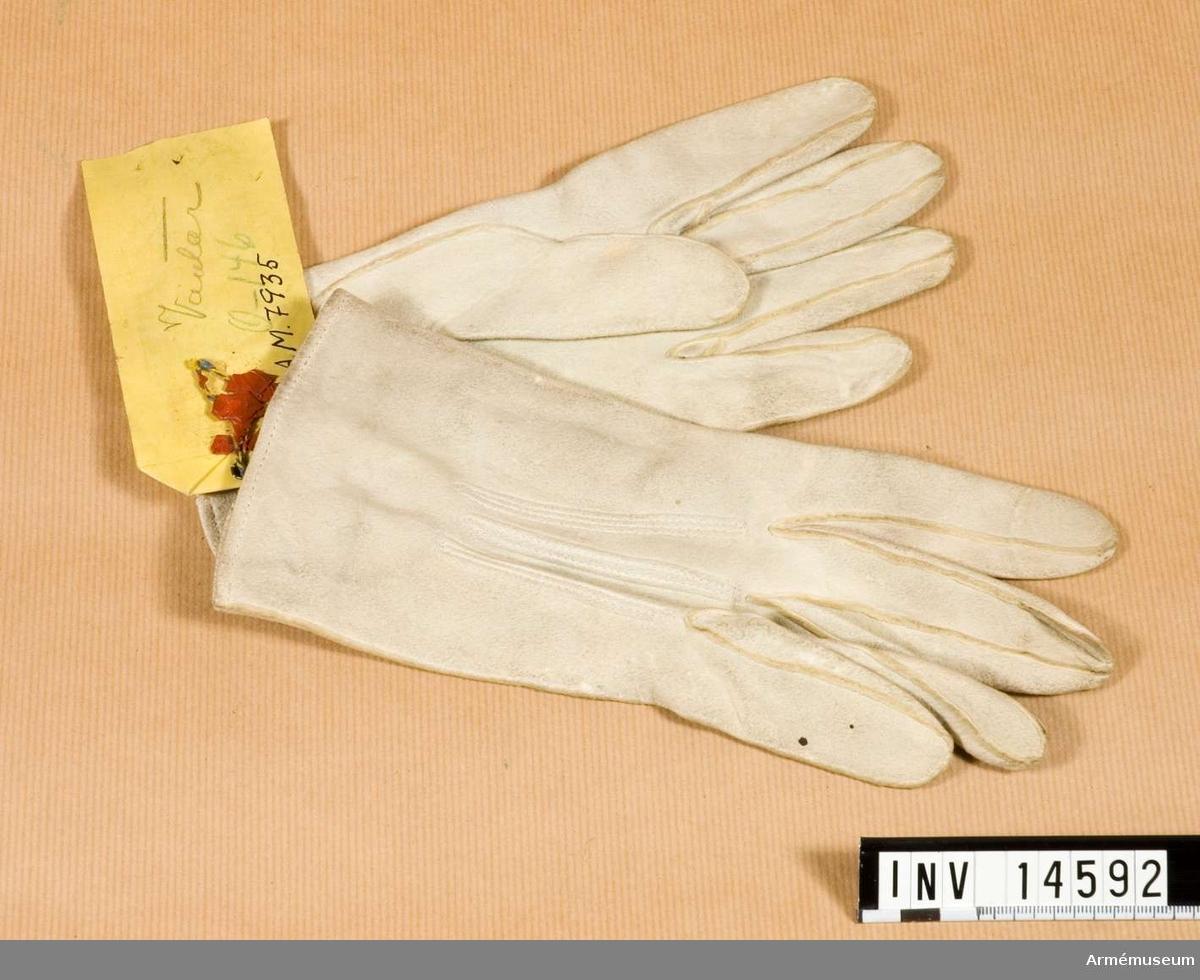 """Grupp C I Handskar av vitt sämskskinn med fem fingrar. Handskarna knäpps med mässingsknapp. På handskarnas innersida stämplar med påskriften: """"WHD"""" (uppåtriktad pil över H) """"1893"""" """"Monly & Gloves"""" (Gloves - handskar) """"Woode & Tock"""" - firmanamn. Handskarna har en pappersetikett med påskriften: """"Generalintendentens expedition DK 170/1894. England. 1 pair Glauves (handskar) Pris: 2 s. 1 d.""""."""