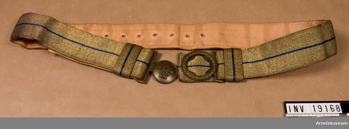 Av bronserad, blått silke och fodrat med naturellt skinn. Spänne av metall i brons, tillverkat av Sporrong.