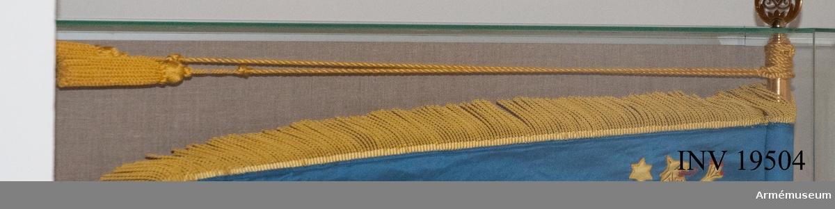 Kordong till standar för Karlsborgs luftvärnsregementes kamratförening. Kordongen och tofsen är båda tillverkad av gul syntettråd.