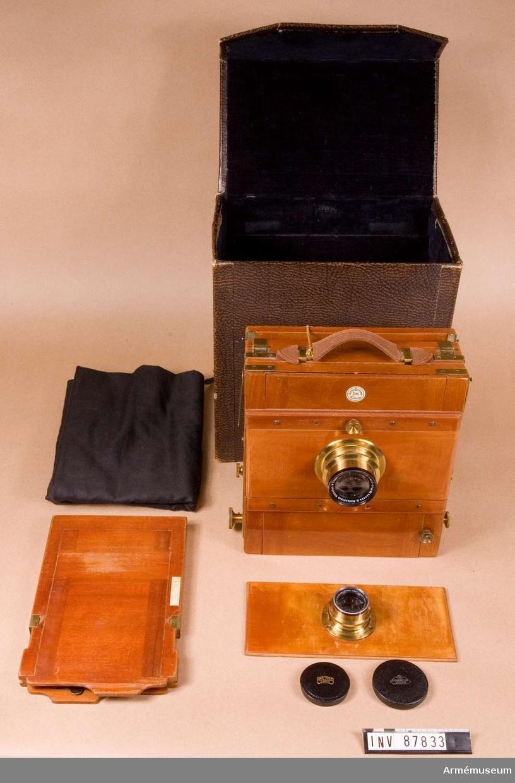 Storbildskamera 9x12 av trä.Består av: 1 kamera, 1 objektivbräda, 1 inställningsduk av svart bomull, 1 stativ m kuggdrev (trä), l:750 mm, vikt:4100 gr. 1 förvaringslåda, 275x175x290 mm, vikt:1500 gr.