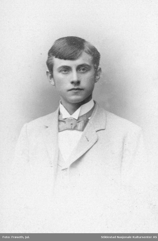 Portrett av ukjent gutt/ungdom med lys jakke og vest, samt sløyfe i halsen.