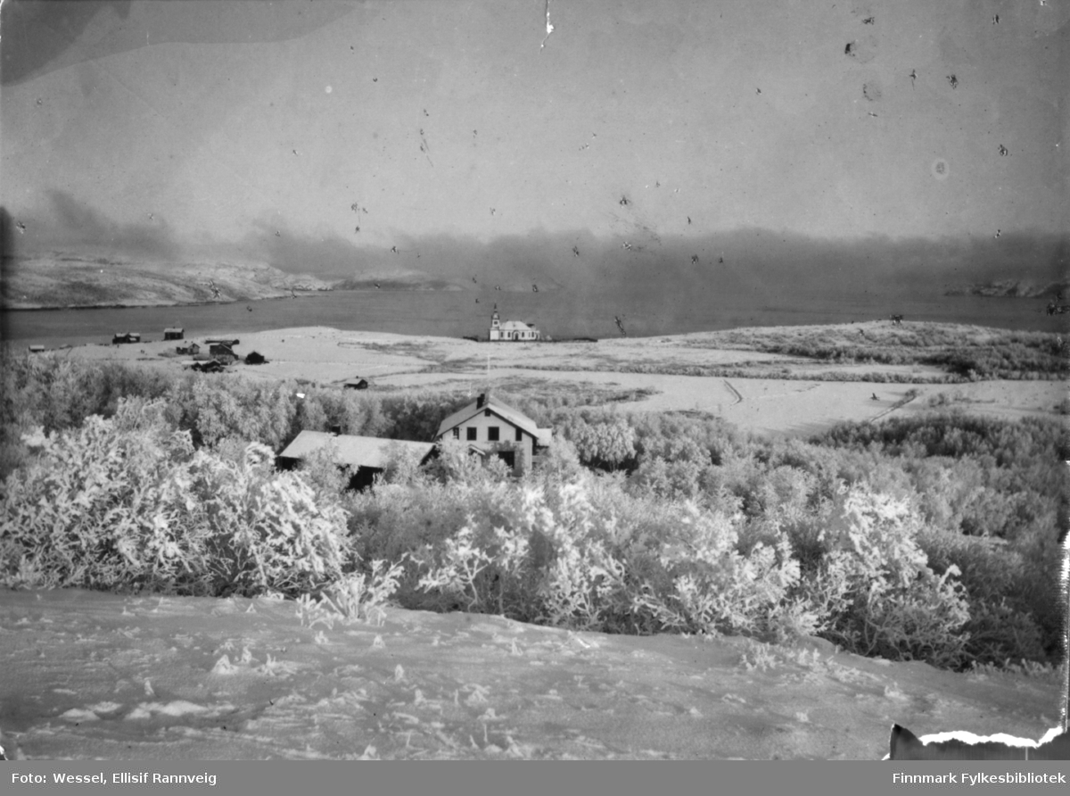 Bildet tatt fra Kirkenes før anlegget kom. Føran i bildet distriktslegeboligen, bak den klokker Anders Tokles gård og lengts bak kirke. Landskapet er dekt av snø.