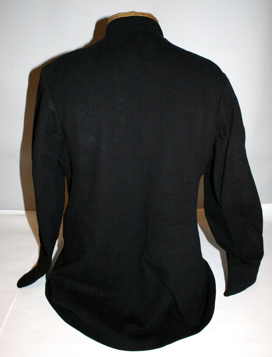 Uniformsjakke i sort med blåskjær med gulfknapping over seks knapper. To brystlommer med klaff. Stående krage kantet med 12 mm gullbånd. Skulderklaffen har et 7 mm gullbånd med en løveknapp og metallnummer romertall 2.