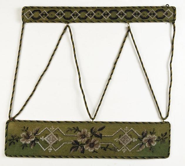 To rektangulære broderte plater bundet sammen. Øverste platen er smalere enn nederste. I øverste er det kroker til oppheng