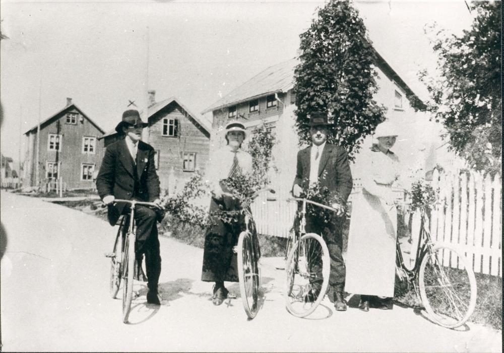 Gatemotiv Toraneset/strandgata. To unge damer og to unge menn m/sykler. Fra venstre : Sverre Fiskum, Olga Olsen, Aksel Høines, og Agneta Torp. Huset i bakgrunnen til venstre som skimtes såvidt, er Aksel Jakobsens hus hvor veien svinger til høyre mot vika. Vår eller sommer.