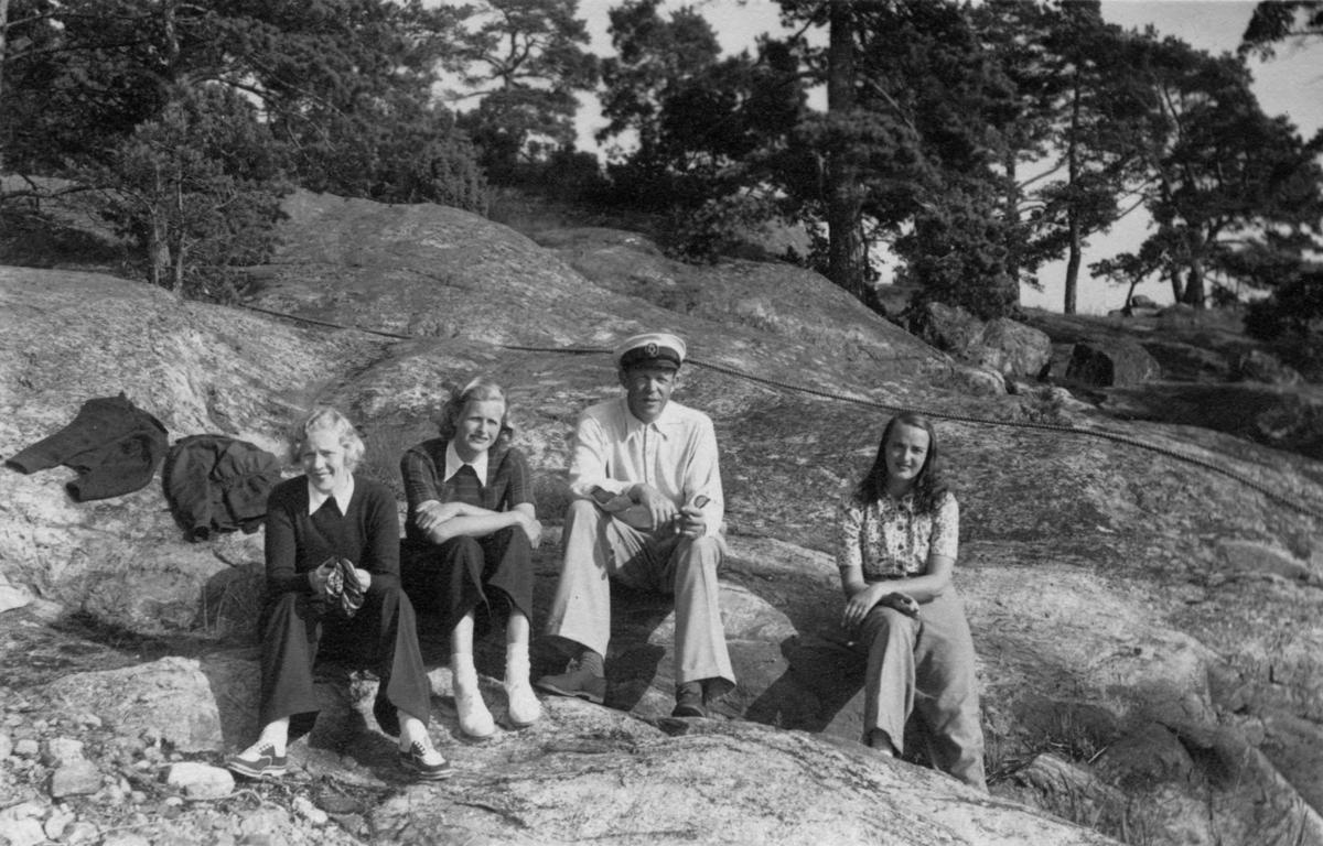 """Övrigt: Från KSSS långfärd till Barösund 11-19 juli 1942; eskaderchefen Gösta Du Rietz omgiven av kvinnliga besättningsmedlemmar. Om långfärden, se KSSS årsbok 1943 s 131 ff; fotografiet återfinns där i beskuret skick på s 136. Det åtföljs av bildtexten: """"Rorsmännen på tre av båtarna hade som uteslutande besättning sina fruar, vilka här ovan komplimenteras av eskaderchefen för gott sjömansskap."""" Jfr bild från samma tillfälle i Till Rors årg. VIII (1942) nr 7 s 219."""