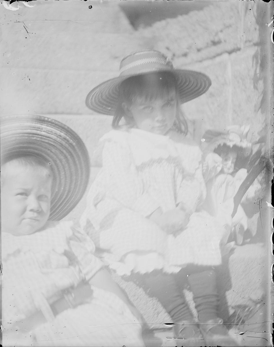 To barn sitter på en steintrapp. Den ene sitter sammen med en dukke.
