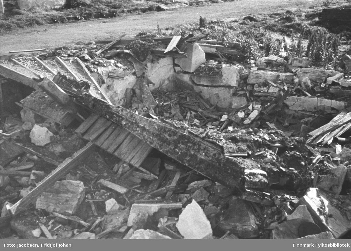 En ruinhaug i sentrum. Rester av en grunnmur står på området. I haugen ligger også stein og betong og deler av brent material og noen planker. Noen viltvoksende blomster står oppe til høyre på bildet. Oppe på bildet ses en grusvei og noen gresstuster ses helt øverst på bildet.