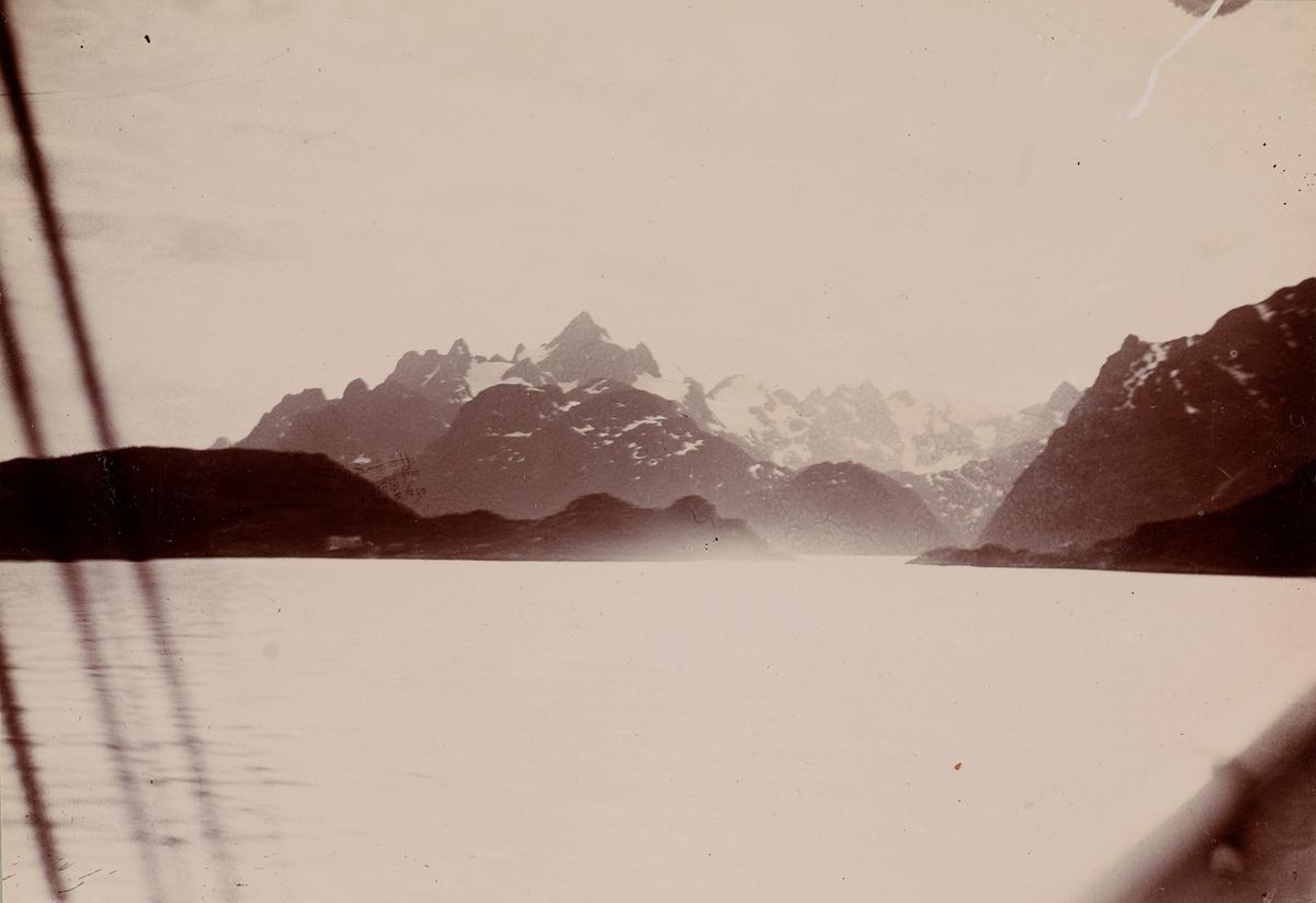 Fjord og snødekte fjell sett fra båten.