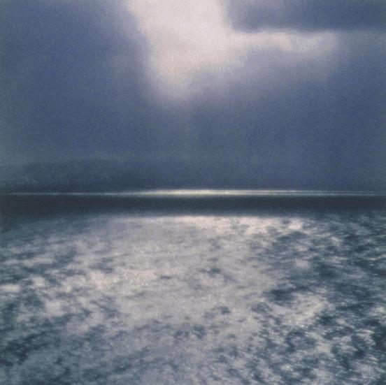 Bildet viser en mørk vinterdag, i det solen såvidt bryter frem mellom skyene. Motivet har en tematisk forankring til havet og en tilknyttning til den norske naturen.