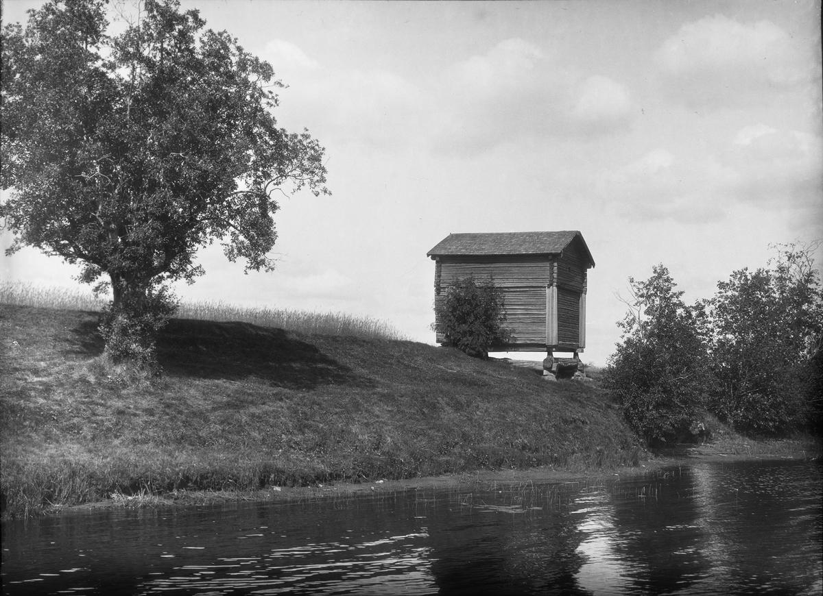 Diapostiv, fönsterbild med motiv från Floda. Litet timmerhus invid vattnet.