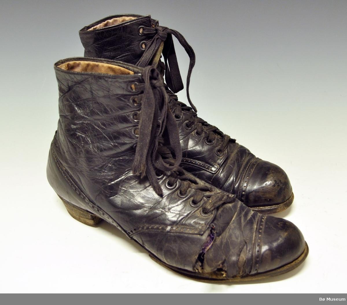 Lærstøvler med hel og snøring brukt til folkedrakt/bunad.Tåhette med dekor langs sømmen  formet som små hull.Samme dekor langs sømmen på sidene. Begge støvlene er  slitt og støvel A har et stort hull på høyre side.