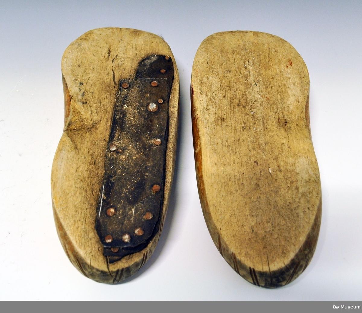 Ett par tresko A og B. Begge har  trebladsdekor på foten og er uten såle under. Tresko B er bygd opp på den ene siden med et stykke lær og festet med 15 stk metallnagler. Innvendig har A spor etter avispapir.