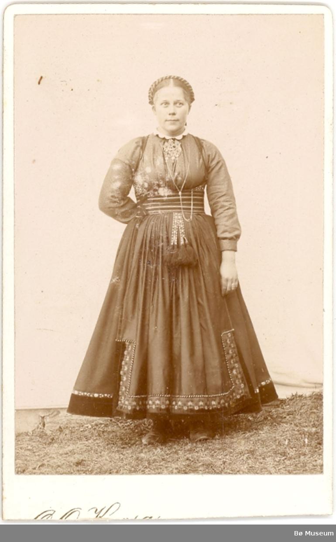 Ukjent kvinne i beltestakk ståande ute i enkelt fotoatelier