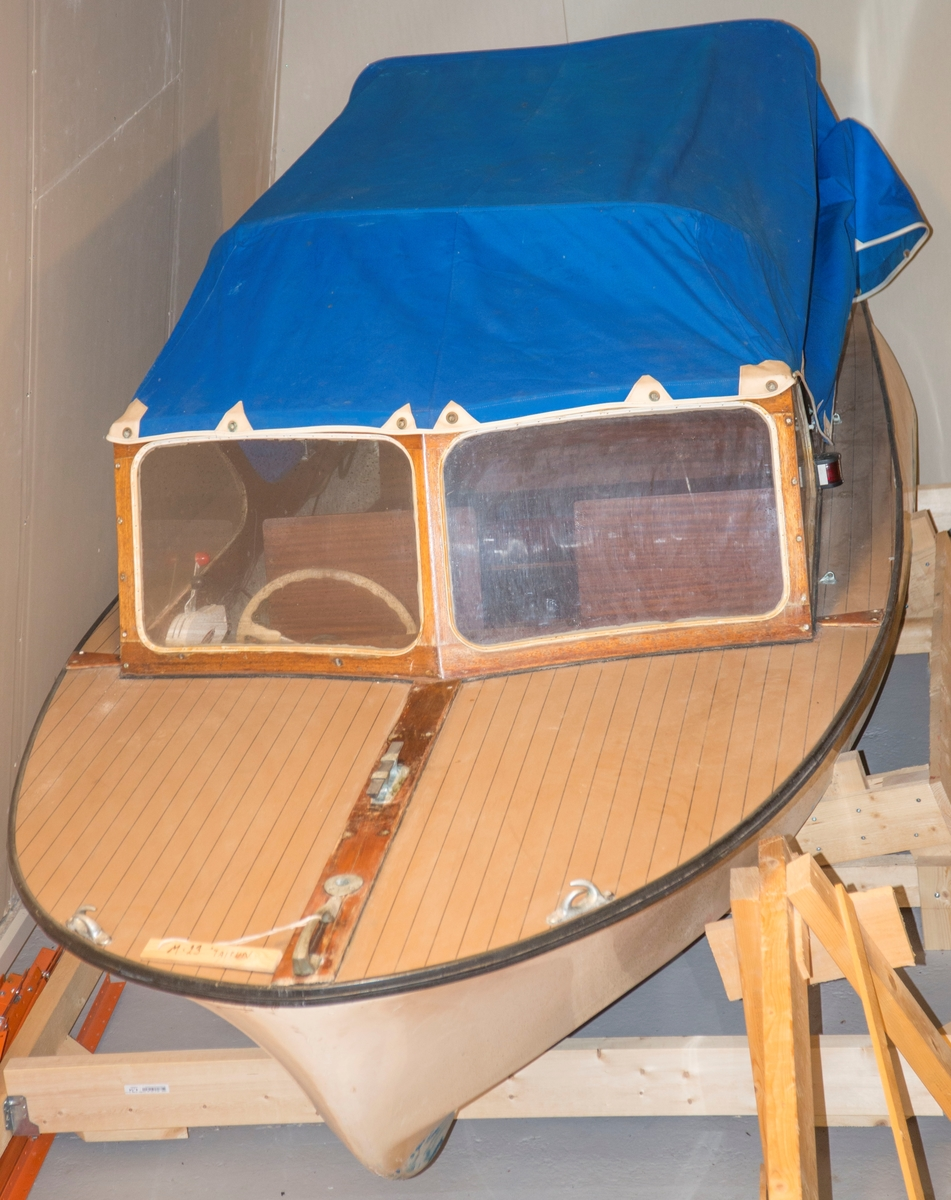 Støpt glassfiberbåt med halvdekk (vinyl) og overbygg. Blå kalesje.