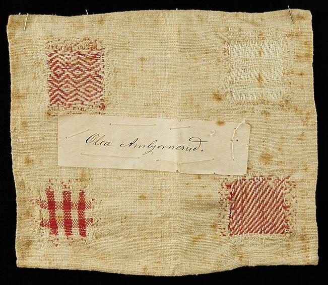 Rektangel. Hvit med rødmønstrede lapper og stopping. Navnelapp i papir påskrevet med sirlig håndskrift: Olea Ambjørnrud