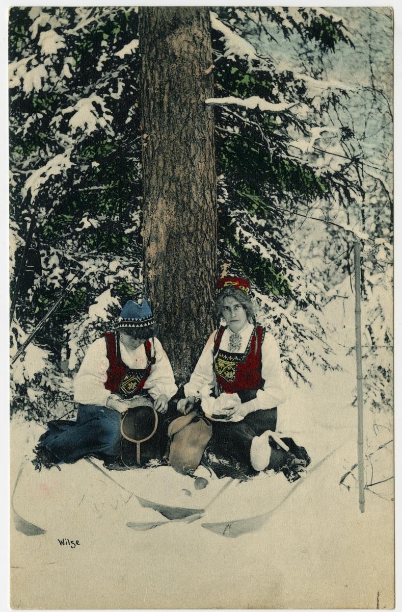 Kolorert postkort. To kvinner i bunad sitter i snøen under et tre.