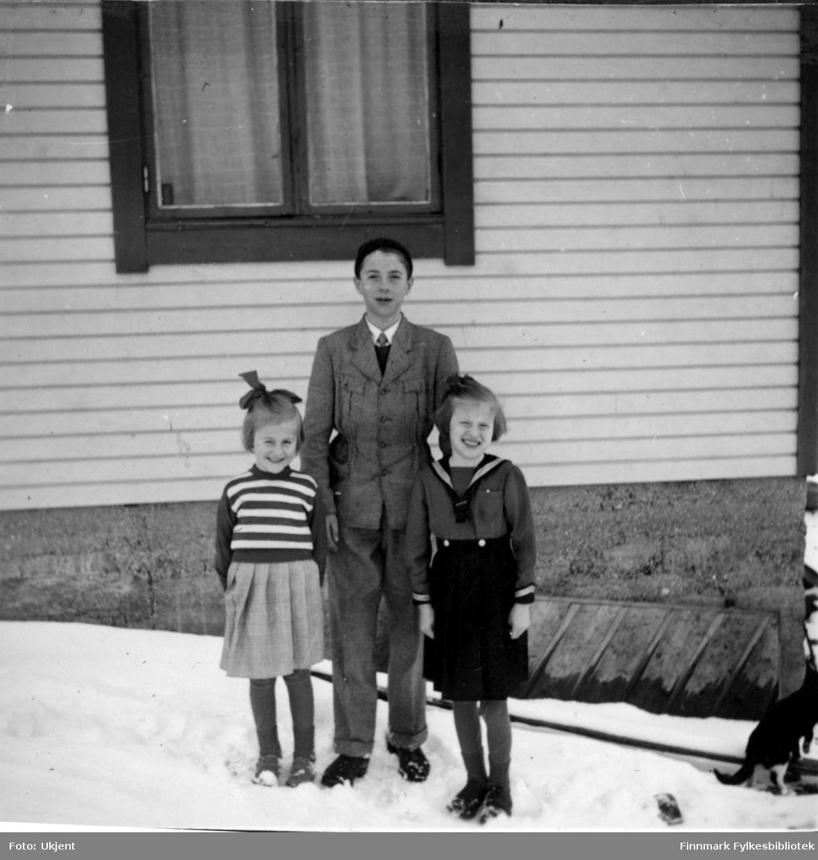 Fra venstre: Randi, Odd og Brynhild Martinsen. Barna poserer foran et hus. Randi har på seg en skjorte, skjørt og strømper. Brynhild har på seg maritim-inspirerte klær: skjorte med sjal på skuldrene, skjørt og strømper. Begge jentene har også på seg sko og en sløyfe i håret. Odd har på seg jakke, lue, slips, bukser og sko. På huset kan man se en grunnmur og et vindu med gardiner i. Helt til venstre kan man se en katt snike rundt hushjørnet. Bakken er dekket til av sne.