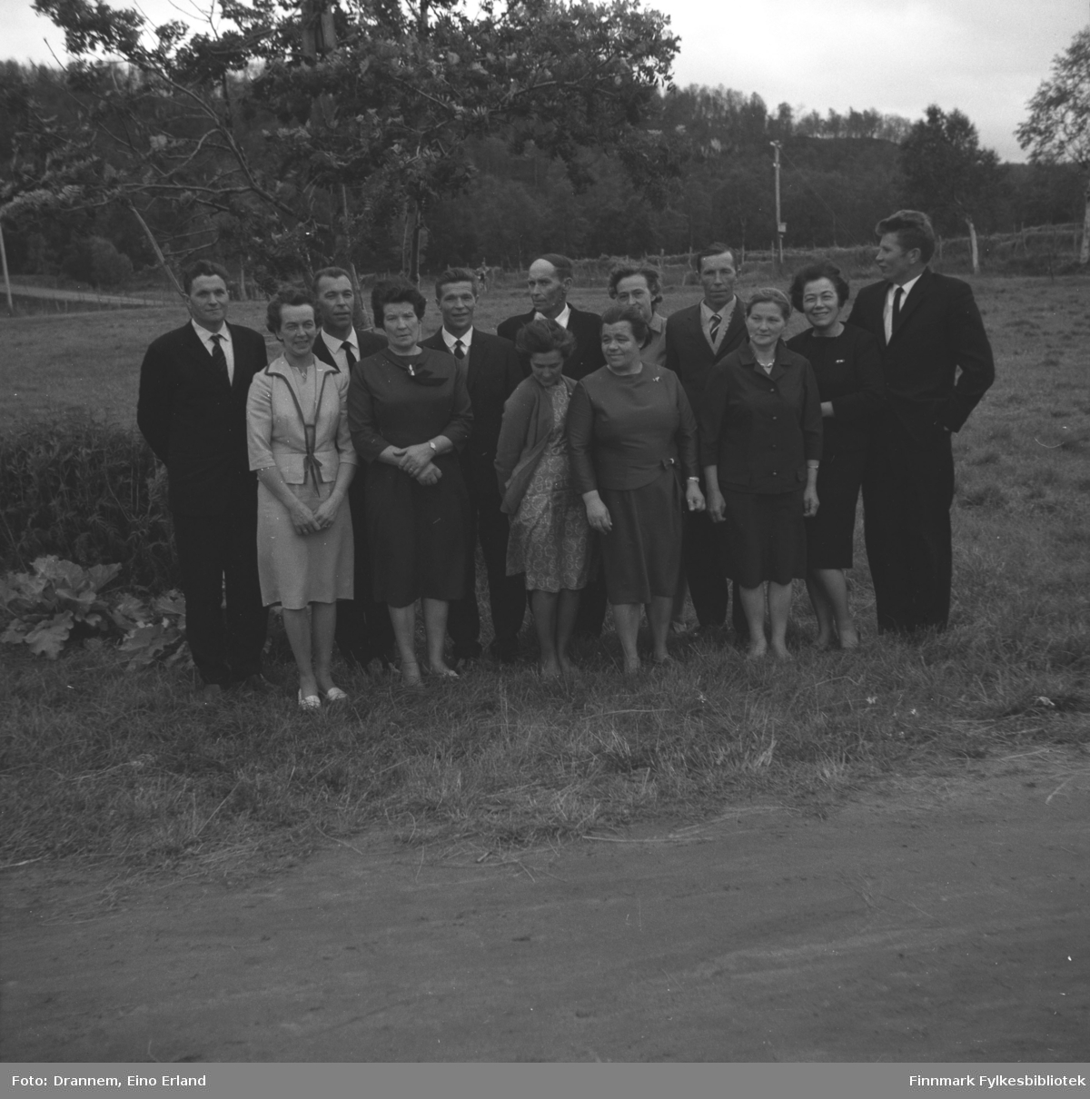 Flere personer i Karikoski-slekten poserer foran et jorde i Neiden sommeren 1965. De er, i bakre rekke fra venstre: Hermann Karikoski, Gunnar Karikoski, Aage Karikoski, Helge Karikoski, ukjent, Arne Karikoski og Oskar Karikoski. Foran fra venstre: Haldis Grunnfoss, Lyyli Arvola, Natalie Karikoski, Aslaug Karikoski, Alette Karikoski og Jenny Drannem.