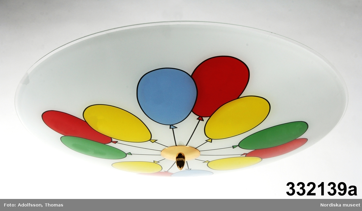 Plafondlampa för takmontering. Kupa av något konvex rund glasskiva i vitt dekorerad med ballonger i gult, rött, blått och grönt. Mässingsdetalj genom skärmens mittpunkt förbunden med lång gängad krok, fixerar glasskärmen vid plåtskiva med tre lampsocklar på lampans baksida. Kroken fungerar också för takmontering. Glödlampor saknas. Tunna korta sladdar på sockelskivans ovansida.  /Emma Nelsson, Maria Maxén 2015-11-11