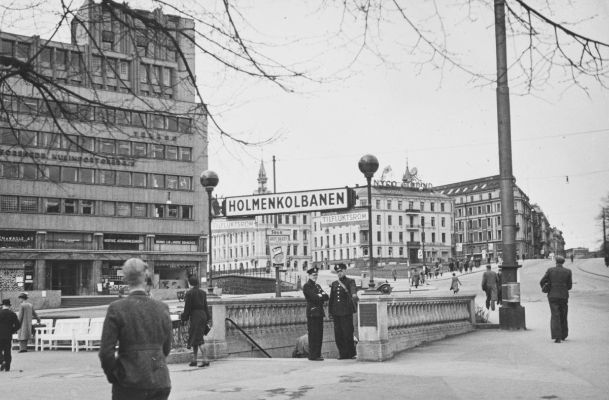 Ved nedgangen til Nationaltheatret stasjon i Oslo. Undergrunnsbanen ble benyttet som ffentlig tilfluktsrom under okkupasjonen. Politikonstabler utstyrt med gassmaske står klar. I bakgrunnen Victoria Terrasse, som ble bombet og delvis ødelagt 25. september 1942 og 31. desember 1944.
