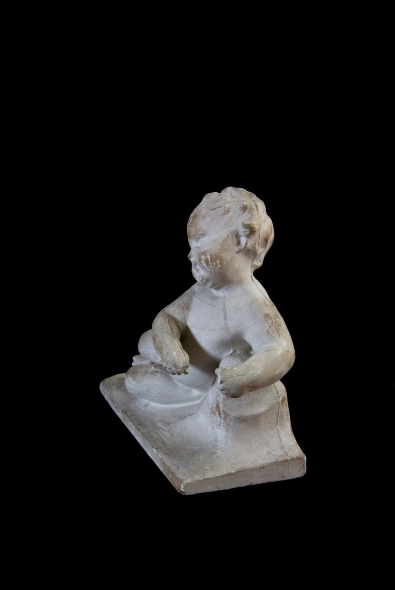 Studiemodell av gips föreställande en liggande putto i helfigur. Lutar sig mot ett stenliknande föremål. På rektangulär platta.