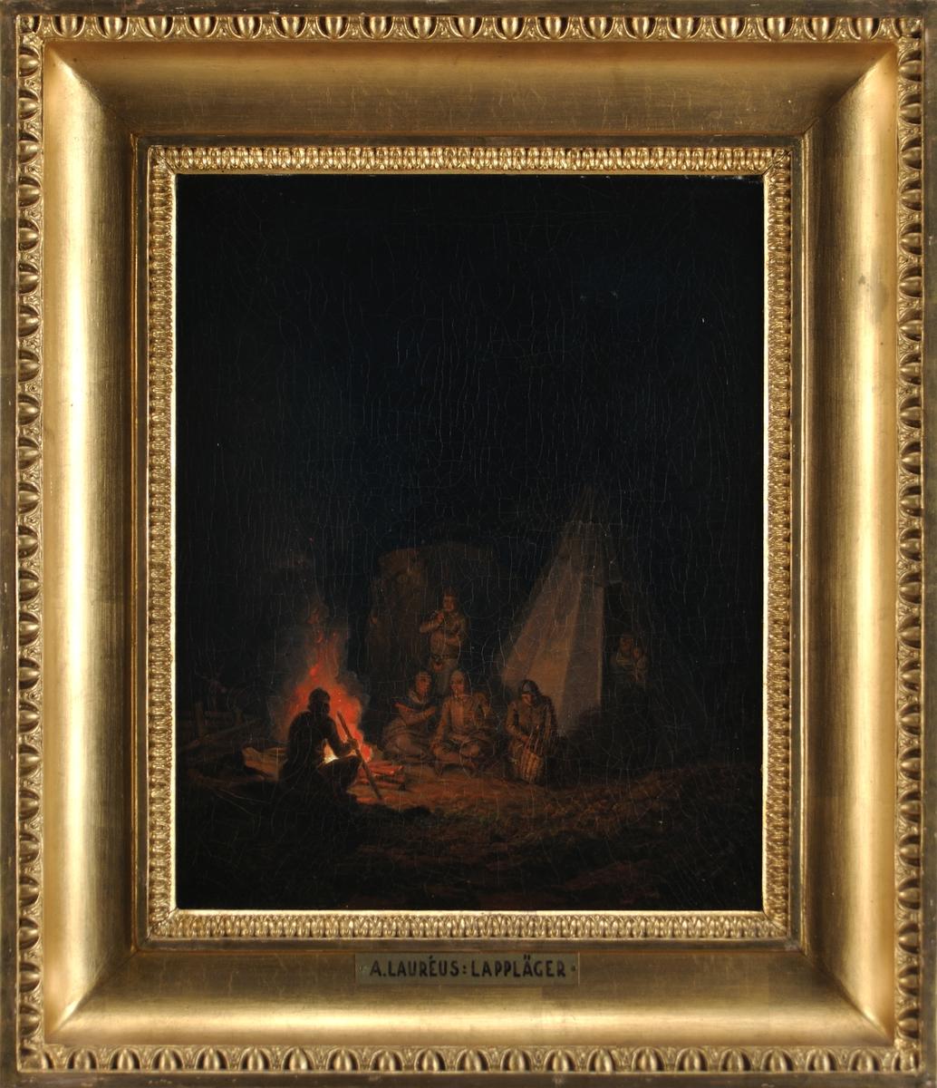 Samisk familj utanför kåta, ett par män röker, en arbetar med en korg. Till vänster flammande eld. Mörk bakgrund. Natt.