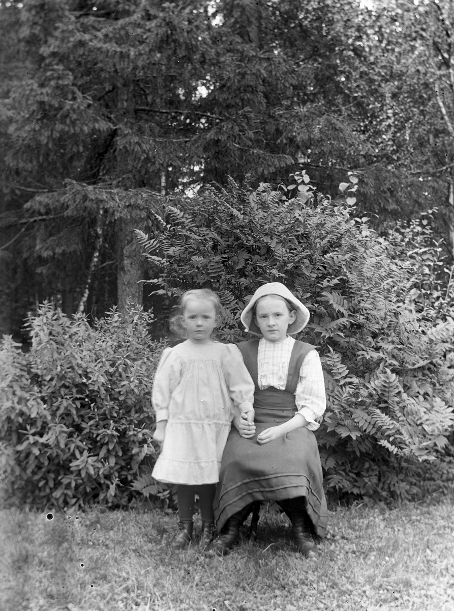 Två flickor i trädgården, troligtvis i Gammelstilla, Torsåker.