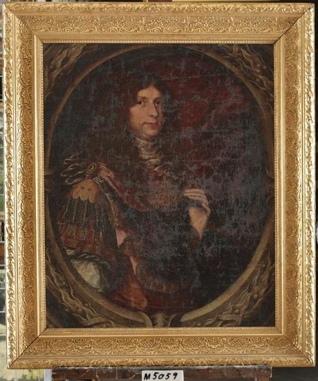 Oljemålning på duk. Porträtt föreställande manlig ståndsperson med mörk peruk och romersk uniform. Mörkbrun bakgrund inom delvis synlig oval av lager. Skall enligt uppgift föreställa kung Fredrik I (?) (1676-1751) .