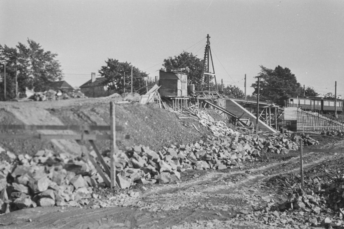 Fra omleggingen av Tryvassbanen og Røabanen ved Majorstuen. Bygging av bro for Røabanen. I bakgrunnen sees en av Holmenkollbanens vogner nr. 105-110.