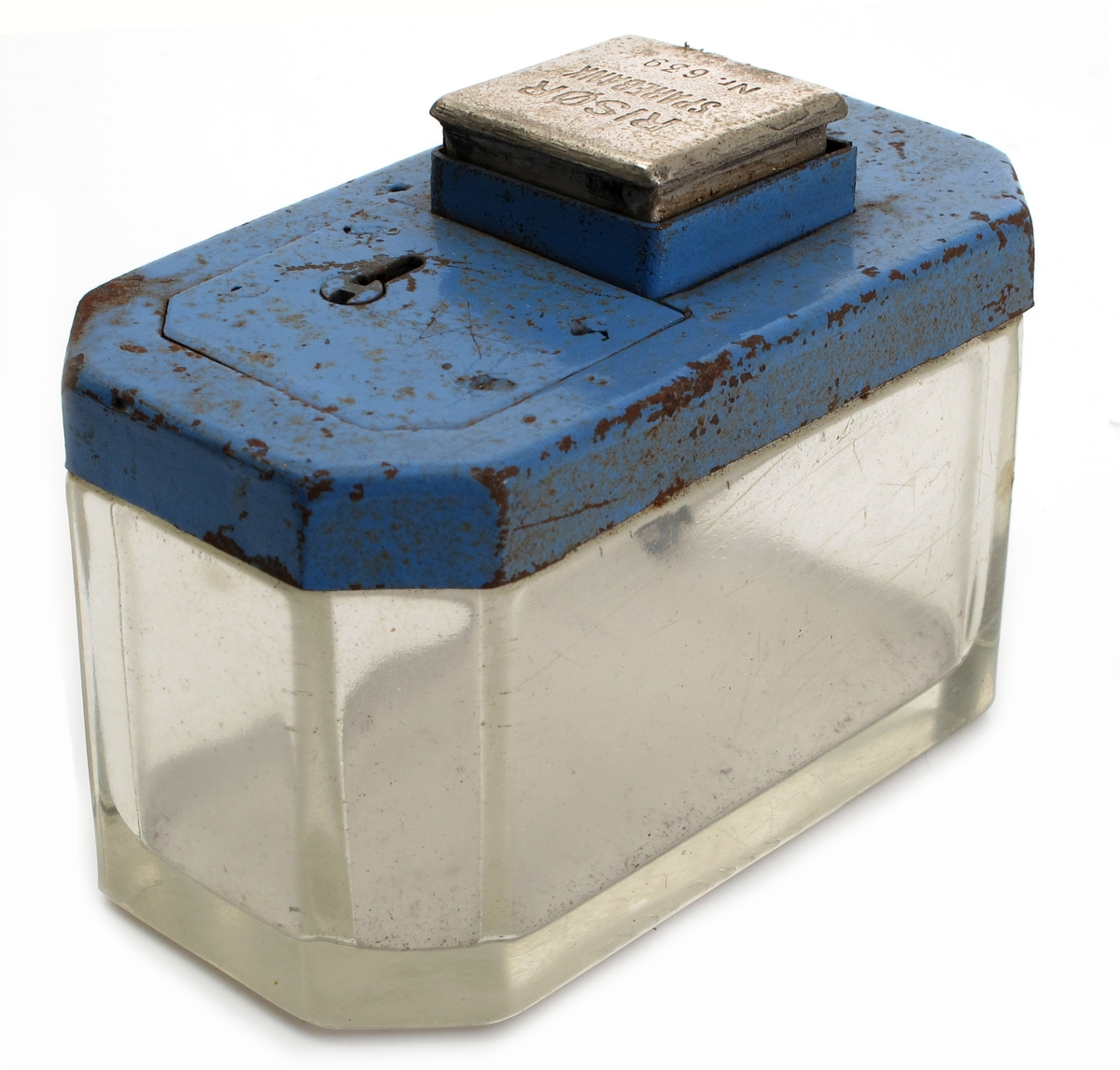 Sparebøsse, Risør Sparebank, 1930-årene. Glass, klart og tykt, støpt.  Lokk av jernblikk, malt  lys blått. Topplokk forkrommet med tekst: Risør Sparebank Nr. 639. Rekangulær dåse med avskårne hjørner i glass, flatt lokk med luke med lås, pm. spalte for innputting av mynt, med et topplokk til å trykke ned.