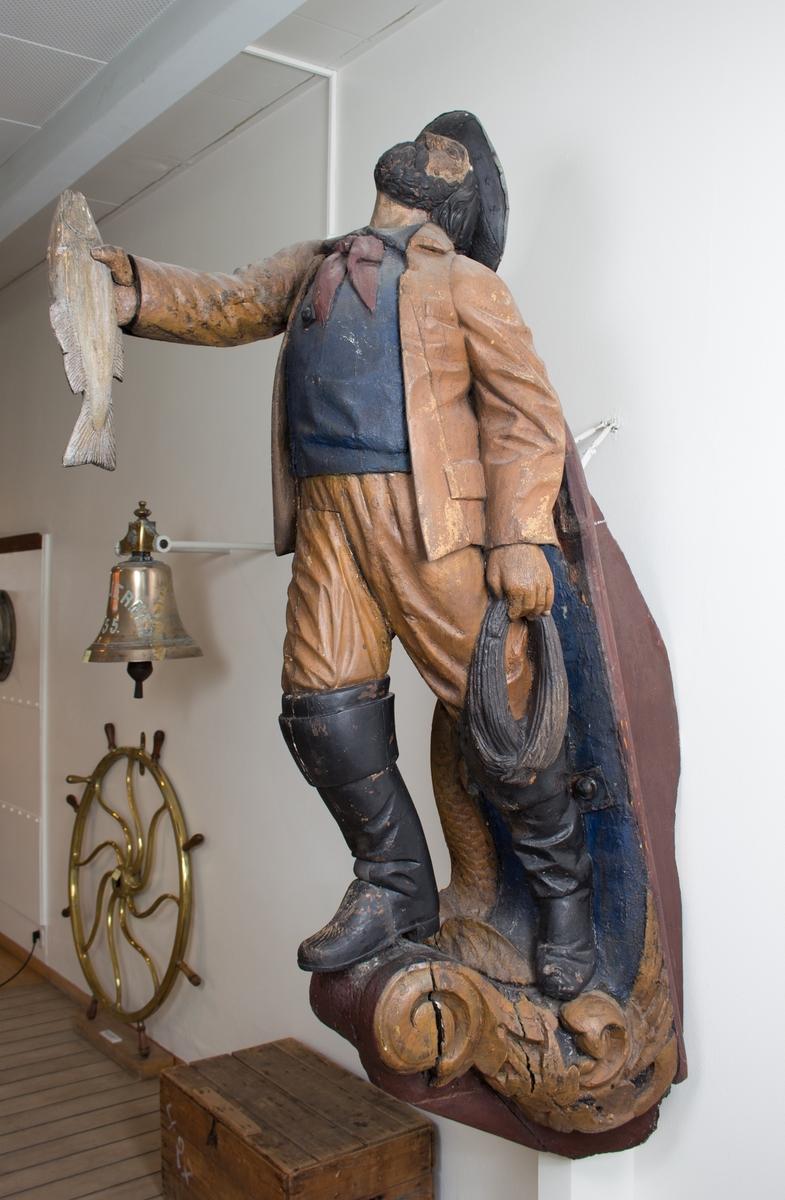 Mannsfigur med fisk i den ene hånden (utstrakt) og en taukveil i den andre.