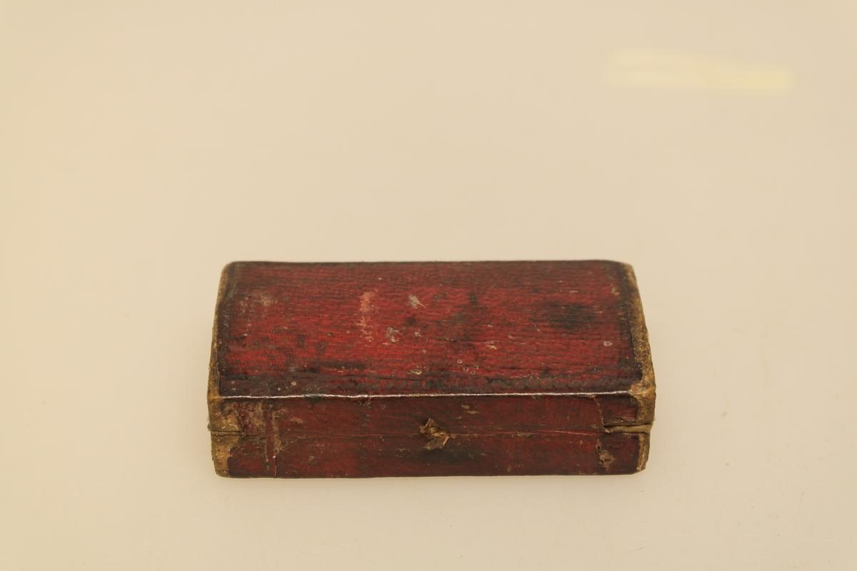 Sneppert (a) med eske (b) til bruk ved årelating.  A) Smidd jernblad og messing. Innrissing av initialer. B) Eske av tynt tre trukket med rødt papir utenpå og brun velour inni. Lukkes med en messinghempe.