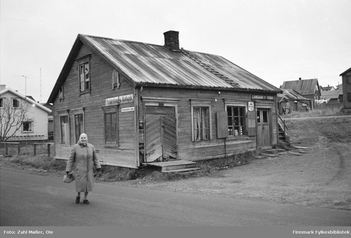 Vadsø, oktober 1969. Gammelt butikklokale med originale butikkskilt. Kvinne i forgrunnen.