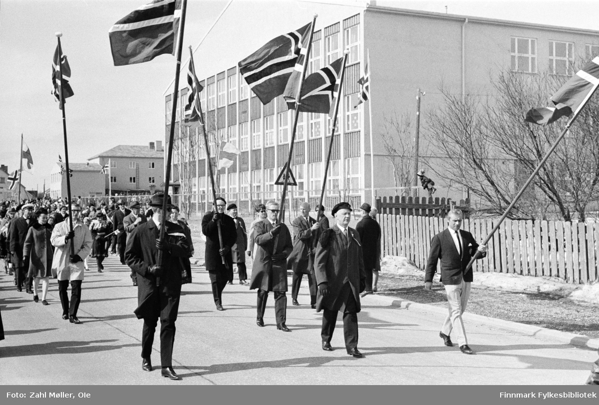 Vadsø 17.5.1969. . Fotoserie av Vadsø-fotografen Ole Zahl-Mölö. Hele 6 flaggbærere leder an i borgertoget. Etter flaggene å dømme er det god vind og skikkert en utfordring å bære flaggene. Litt lenger bak skimtes også et finsk flagg i toget.