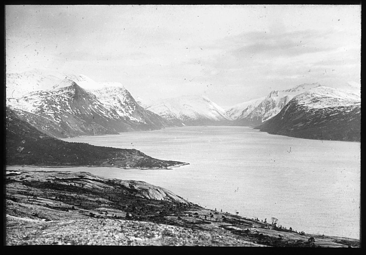 """""""N.567b). Fra Tysfjord."""" Landskapsbilde fra Tysfjord. Bildet viser fjorden omkranset av fjell med snøflekker på. I forgrunnen er det bar mark og sparsomt med vegetasjon."""