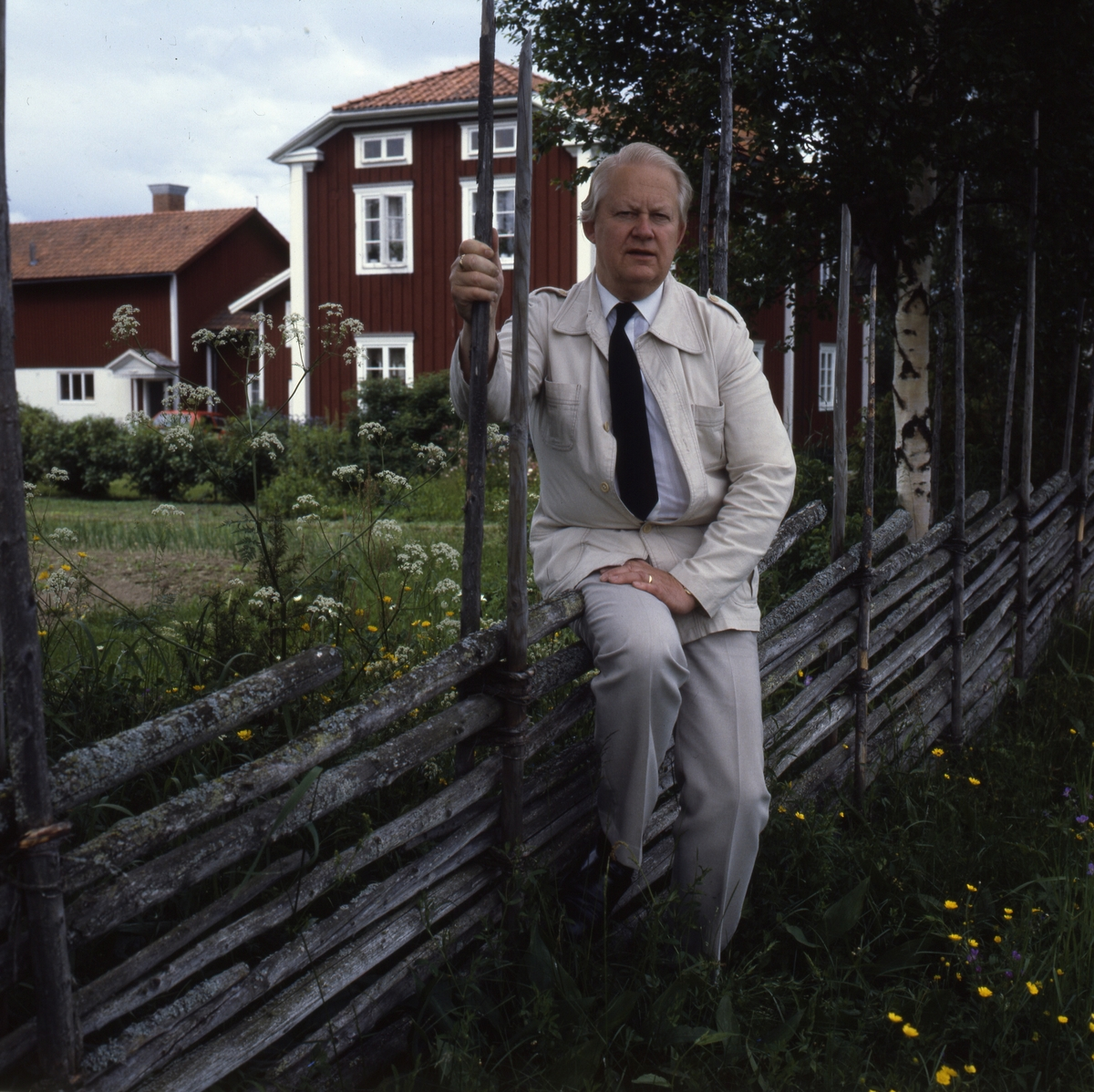 Författaren Bo Setterlind sitter snett över en gärdesgård iförd en ljus kostym och mörk slips. I bakgrunden syns gården Sunnanåker.